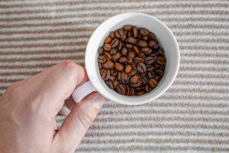 La tazza con i chicchi di caffè su fondo grigio ha barrato la struttura fotografia stock