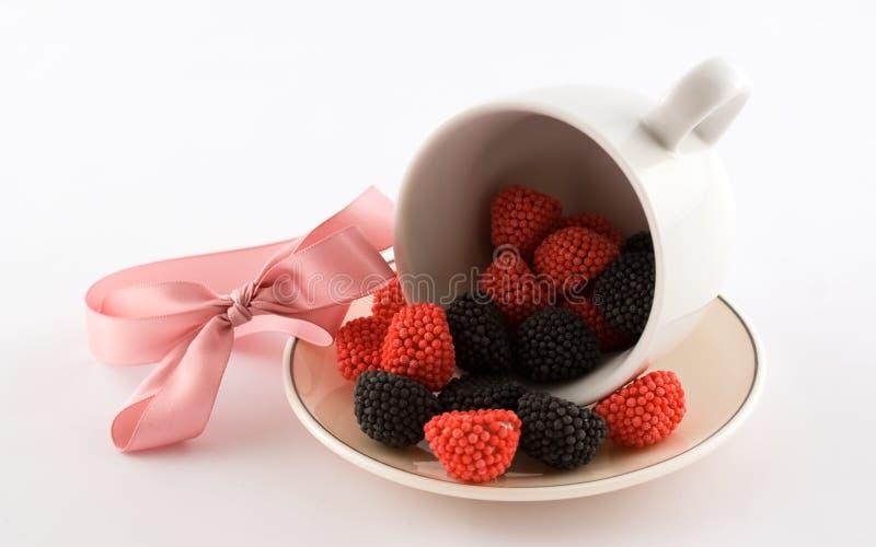 La tazza con l'arco di colore rosa e della caramella immagine stock