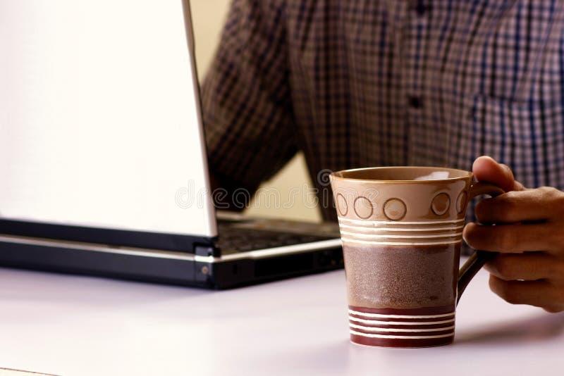 La tazza da caffè ha tenuto dall'uomo che lavora ad un computer portatile nei precedenti fotografia stock