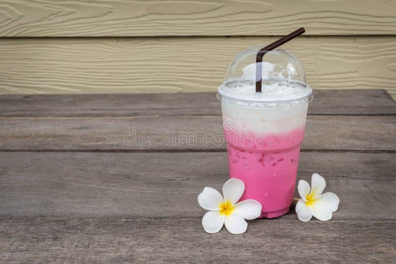 La tazza del latte ghiacciato rosa vicino alla plumeria fiorisce sul pavimento di legno immagini stock