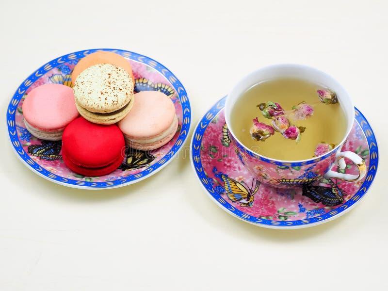 La tazza del tè rosa del germoglio in una tazza abbastanza floreale è servito con i macarons francesi immagini stock libere da diritti
