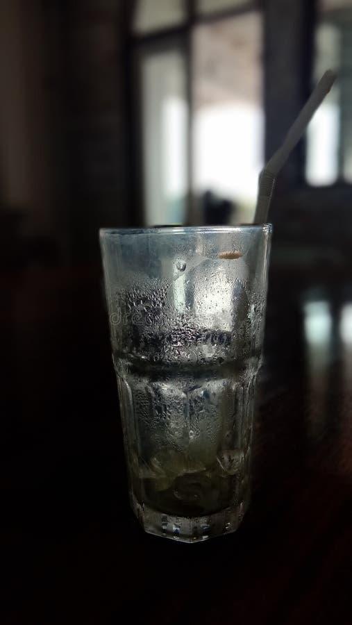La tazza dell'acqua di vetro sulla tavola di legno ha l'illuminazione del fondo immagine stock