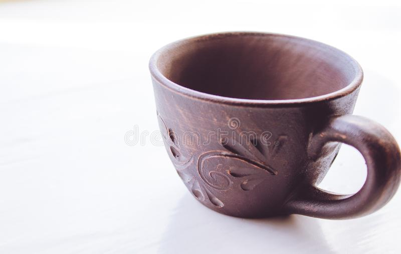 La tazza dell'argilla sta su un fondo bianco immagine stock