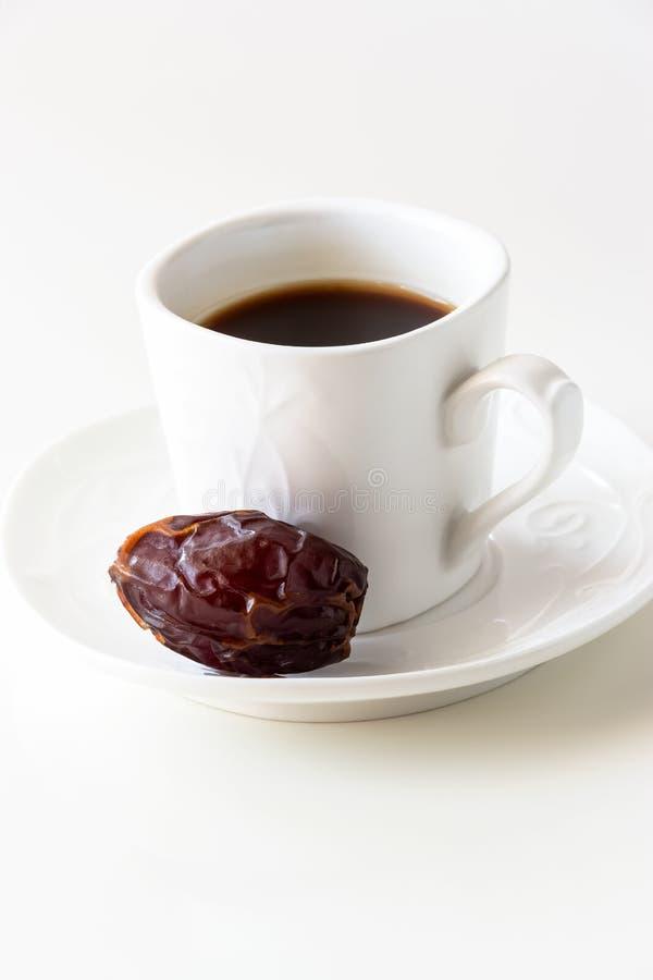 La tazza di caffè bianca ed una data il fondo bianco isolato fotografia stock