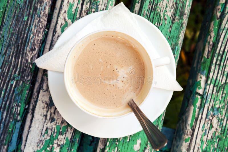 La tazza di caffè con crema è sul vecchio banco di legno fotografia stock