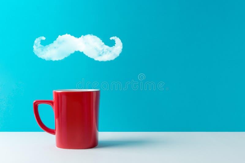 La tazza di caffè con vapore ha modellato dei baffi sulla tavola bianca fotografia stock