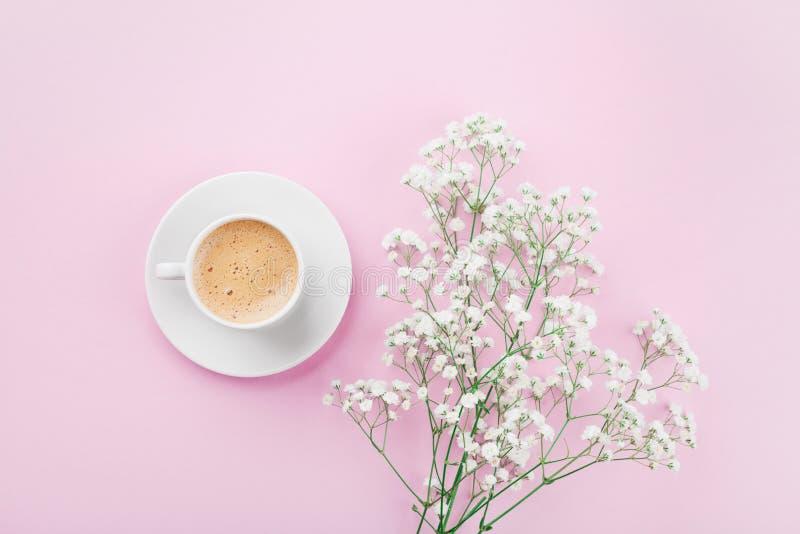 La tazza di caffè di mattina ed i fiori bianchi sulla vista rosa del piano d'appoggio in piano pongono lo stile Bella prima colaz fotografia stock libera da diritti