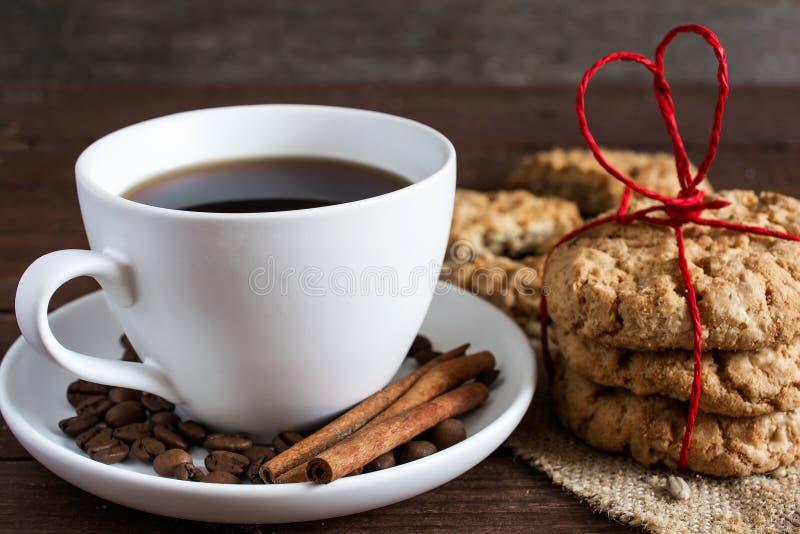 La tazza di caffè ed i biscotti casalinghi legati con cuore hanno modellato il nastro rosso fotografie stock libere da diritti