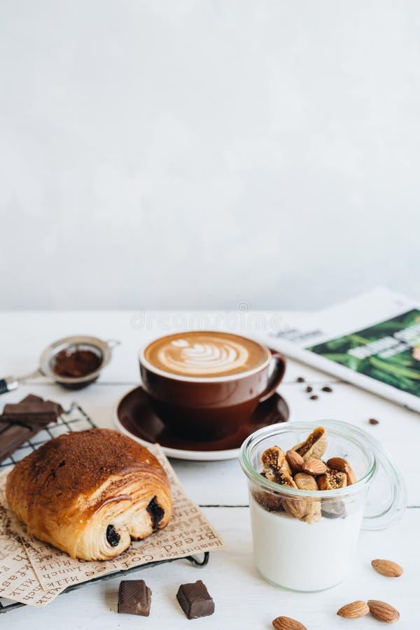 La tazza di caff?, yogurt con i frutti secchi e croissant del cioccolato alla tavola bianca immagini stock