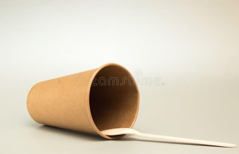 La tazza di carta per le bugie del caffè dal suo lato su un fondo scuro, accanto è un cucchiaio di caffè di legno fotografie stock libere da diritti