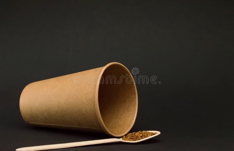La tazza di carta vuota per le bugie del caffè dal suo lato su un fondo scuro, accanto è un cucchiaio di legno con caffè fotografia stock