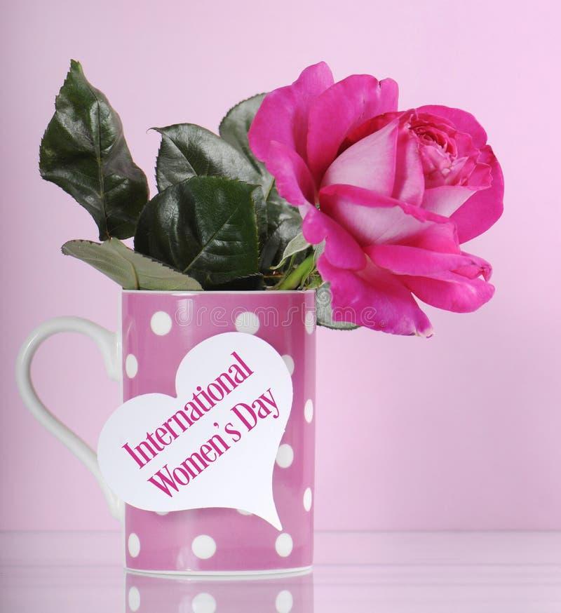 La tazza di Giornata internazionale della donna ed è aumentato immagine stock