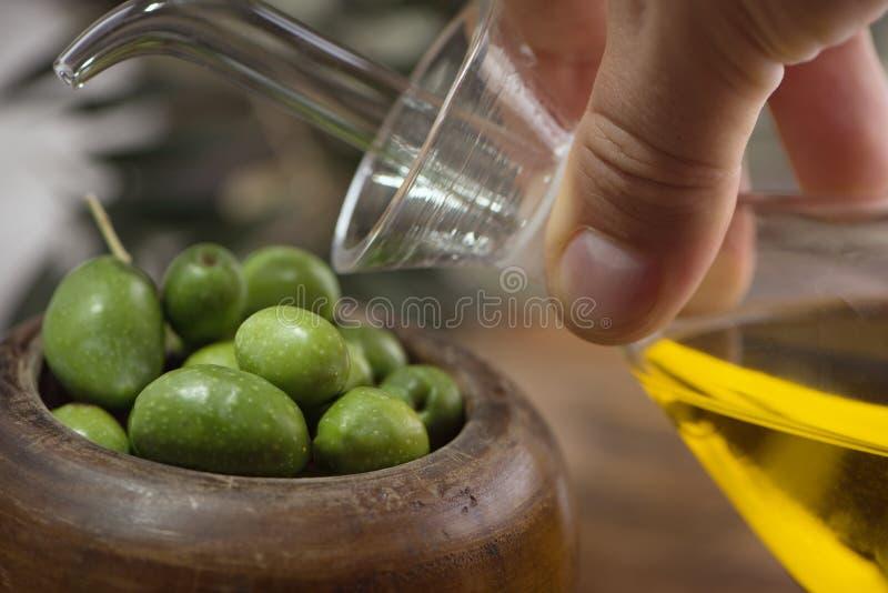 La tazza di legno delle olive con olio d'oliva vergine extra in vetro imbottiglia la mano su fondo rustico Esaminando macchina fo immagini stock libere da diritti