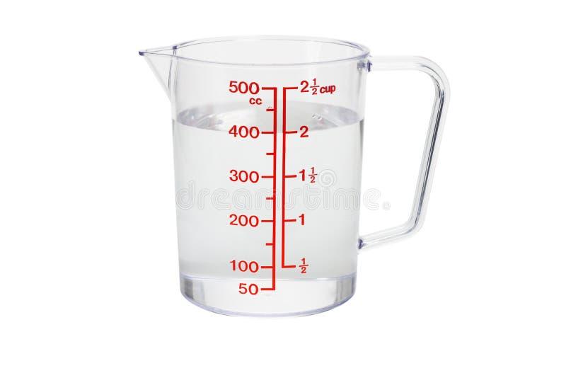 La tazza di misurazione di plastica della cucina ha riempito di acqua fotografia stock