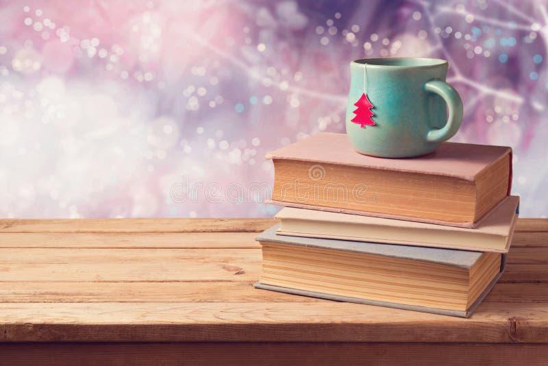 La tazza di Natale di tè e dell'annata prenota sulla tavola di legno sopra il bello fondo del bokeh dell'inverno con lo spazio de immagine stock