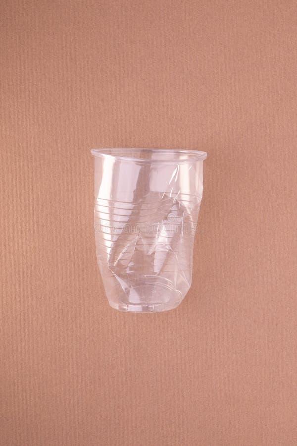 La tazza di plastica schiantata su beige abbronza il fondo Concetto di plastica di utilizzazione Problema ecologico, ambiente glo fotografia stock