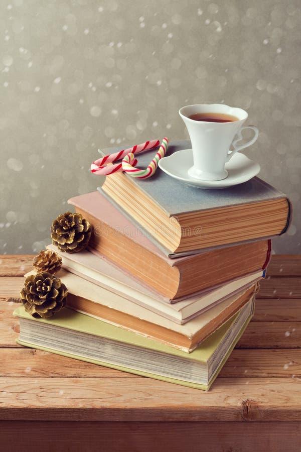 La tazza di tè di festa di Natale sui vecchi libri con amore ha modellato la caramella sopra fondo vago Celebrazione di natale immagine stock libera da diritti