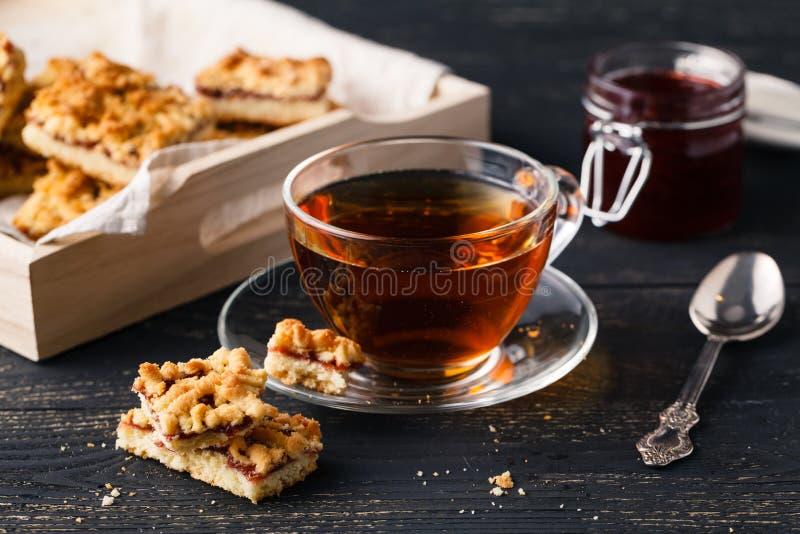 La tazza di tè e del canestro con i biscotti è servito per la prima colazione su woode fotografia stock