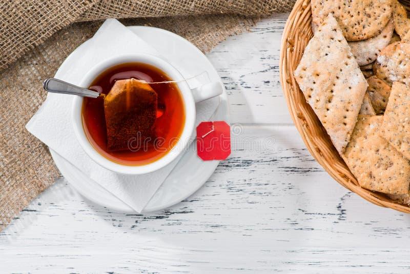 La tazza di tè e del canestro con i biscotti è servito per la prima colazione su woode fotografie stock