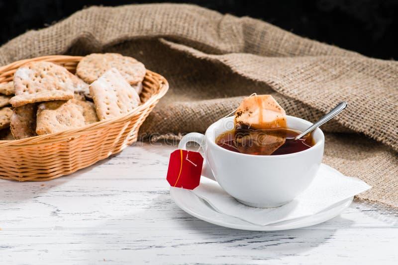 La tazza di tè e del canestro con i biscotti è servito per la prima colazione su woode fotografia stock libera da diritti
