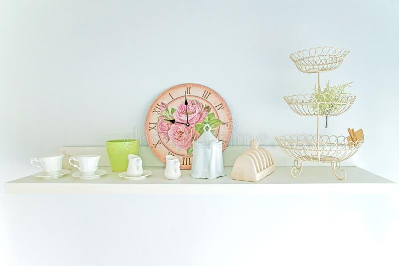 La tazza di tè, orologio e decora l'annata in scaffale fotografia stock libera da diritti