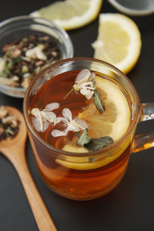 La tazza di vetro di tisana con l'acacia fiorisce, limone, miele su fondo nero, la vista superiore, spazio della copia Freddezza  fotografie stock libere da diritti