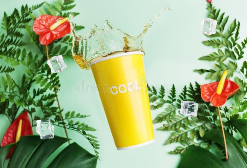 La tazza gialla con i solashes del tè su fondo tropicale con l'anturio rosso della calla foglie fiorisce, della felce e di monste fotografia stock libera da diritti
