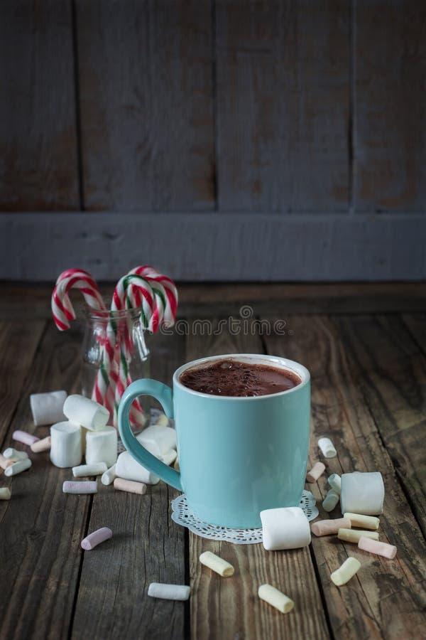 La tazza ha riempito di chocolat caldo vicino alla caramella gommosa e molle ed ai bastoncini di zucchero i fotografie stock