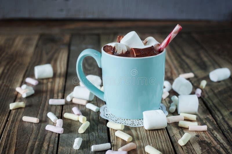 La tazza ha riempito di cioccolata calda e caramella gommosa e molle e bastoncini di zucchero fotografie stock libere da diritti