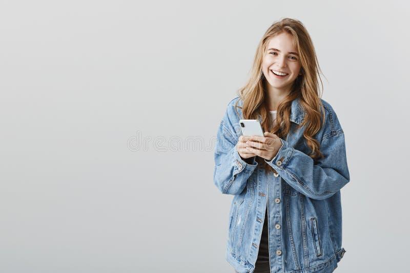 La tecnología es diversión Retrato de la mujer caucásica atractiva feliz satisfecha en chaqueta del dril de algodón que sonríe al foto de archivo