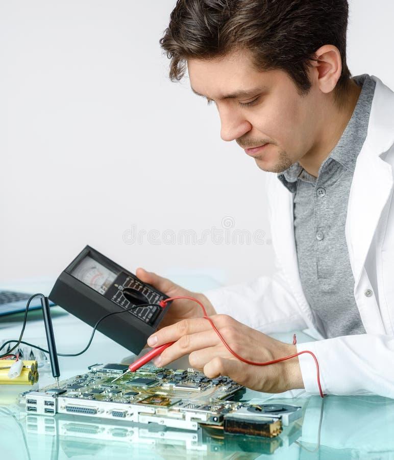 La tecnología masculina enérgica joven o el ingeniero repara el equipme electrónico imagen de archivo libre de regalías