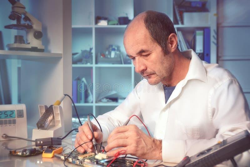 La tecnología masculina mayor prueba el equipo electrónico imagen de archivo