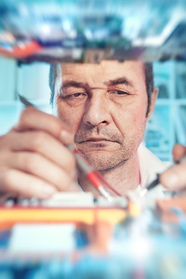 La tecnología masculina mayor prueba equipmen electrónicos imagen de archivo libre de regalías