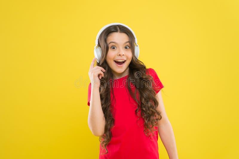 La tecnologia è meravigliosa quando funziona Bambina felice che ascolta la musica in cuffie su fondo giallo piccolo immagini stock