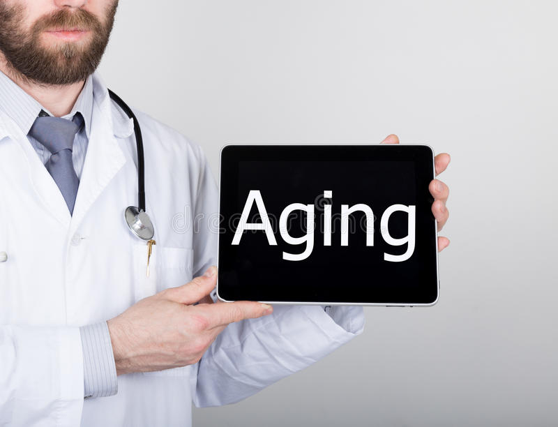 La tecnologia, Internet e rete nel concetto della medicina - aggiusti la tenuta del pc della compressa con il segno di invecchiam fotografie stock libere da diritti