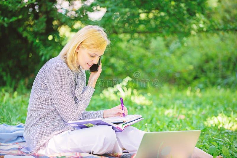 La tecnologia moderna d? pi? opportunit? di realizzare il vostro potenziale Donna con funzionamento dello smartphone e del comput fotografie stock