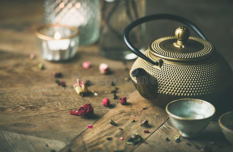La teiera dorata del ferro, tazze, secche è aumentato, candele sopra fondo di legno fotografia stock libera da diritti