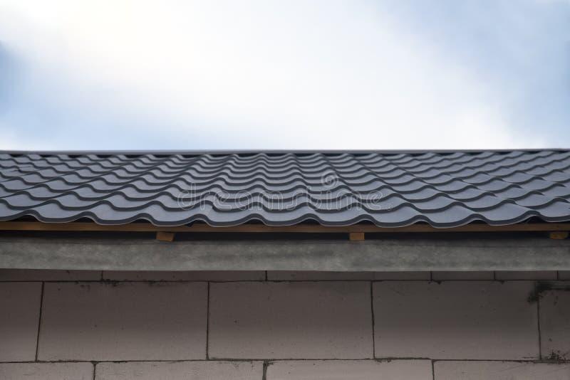 La teja metálica en el techo de la casa es gris imágenes de archivo libres de regalías