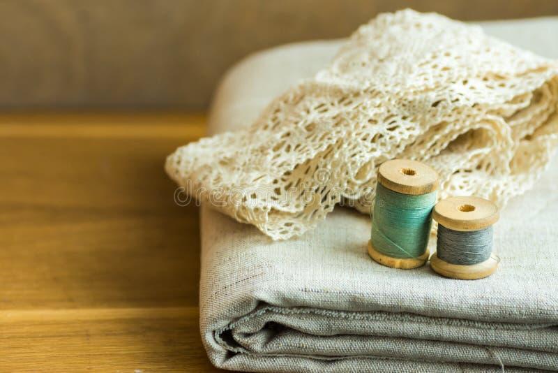 La tela de lino doblada, cintas del cordón, rosca los carretes de madera en la tabla, cosiendo, afición, concepto de la moda imagen de archivo libre de regalías