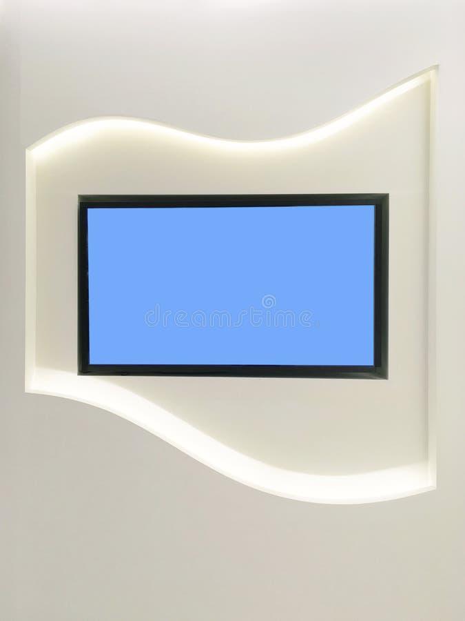 La televisione dello schermo blu del primo piano alla parete di legno bianca ha strutturato il fondo nel bello concetto interno fotografia stock