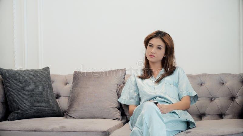 La televisione di sorveglianza della giovane donna e tiene un telecomando immagini stock