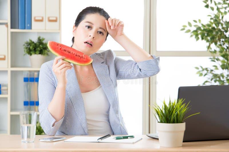 La temperatura è troppo alta in ufficio, donna sta sudando fotografie stock