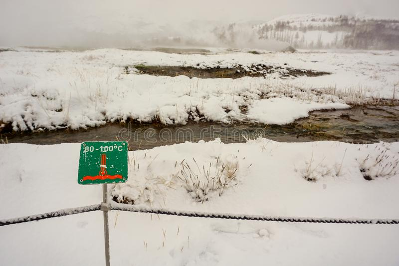 La temperatura en esta área geotérmica podría ser hasta 100 grados, aunque sea invierno y todo se cubre en nieve foto de archivo