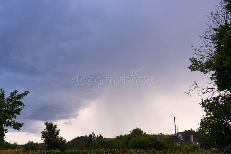 La tempesta di sera si rannuvola il paesaggio del villaggio fotografia stock libera da diritti