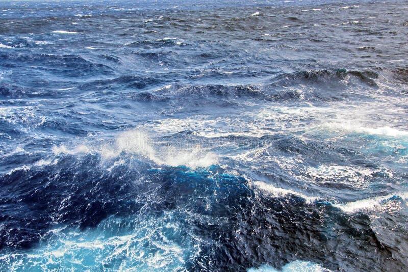 La tempesta ondeggia nell'oceano del mondo Il genere di onde, crests, spruzza, schiuma contro lo sfondo del mare e cielo blu fotografia stock libera da diritti
