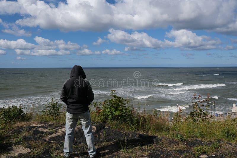 La tempesta sta venendo Un uomo solo sta stando su davanti al Mar Baltico che sta facendo le onde immagine stock libera da diritti