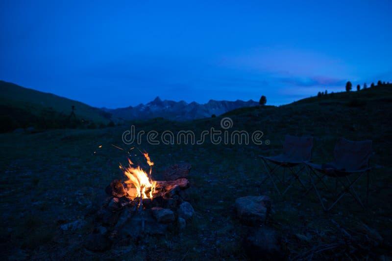 La tenda ed il campo bruciante infornano al crepuscolo sulle montagne Avventure ed esplorazione di estate nelle alpi Fuoco selett immagini stock