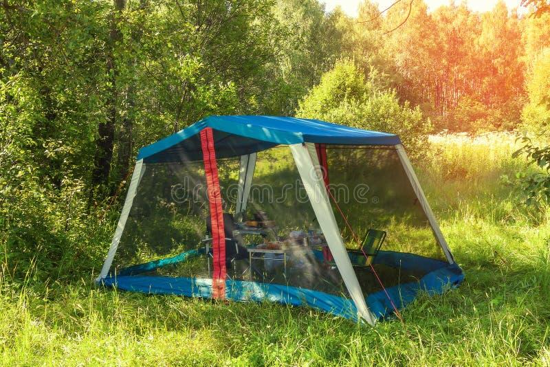 La tenda turistica sta nel legno nel prato di estate fotografia stock
