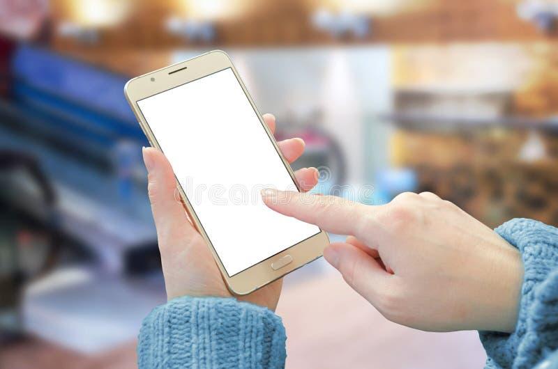 La tenencia de la mujer y la exhibición elegante del teléfono del tacto con blanco, esconden la pantalla aislada para la maqueta fotos de archivo libres de regalías