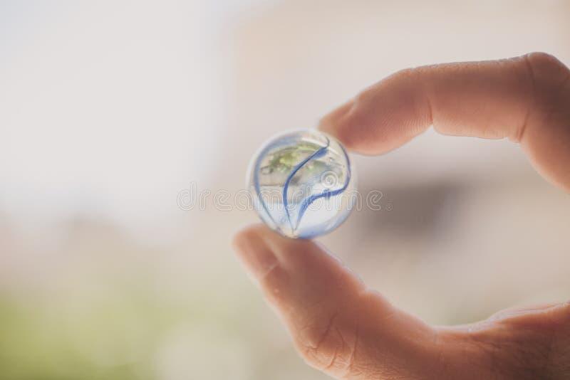 La tenencia de la mano vetea bolas en fondo de la luz del sol Mármoles de cristal a disposición foto de archivo libre de regalías
